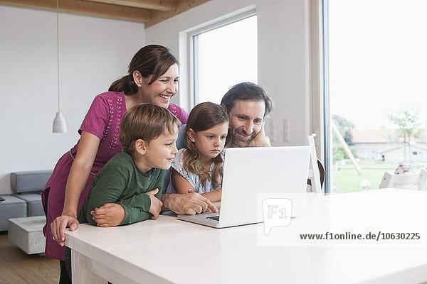 Glückliche Familie beim gemeinsamen Surfen im Internet mit dem Laptop