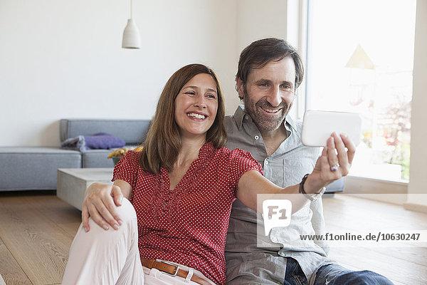 Erwachsenes Paar  das auf dem Boden sitzt und Selfie mit Smartphone nimmt.
