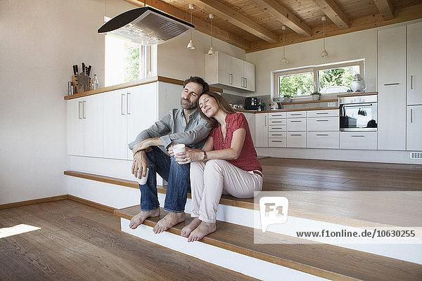 Das reife Paar sitzt auf dem Boden  die Frau lehnt den Kopf auf die Schulter des Mannes.