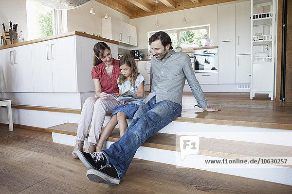 Glückliche Familie sitzend auf Küchenstufen  Eltern lesen Buch mit Tochter