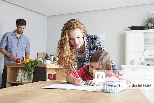 Kleines Mädchen bei den Hausaufgaben am Küchentisch mit ihren Eltern im Hintergrund