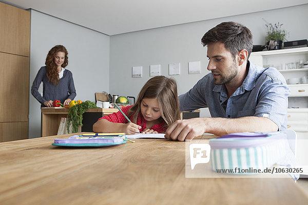 Kleines Mädchen macht Hausaufgaben am Küchentisch  während ihr Vater sie beobachtet.