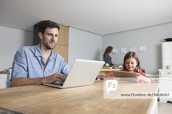 Mann und seine kleine Tochter sitzen am Küchentisch mit Laptop und digitalem Tablett