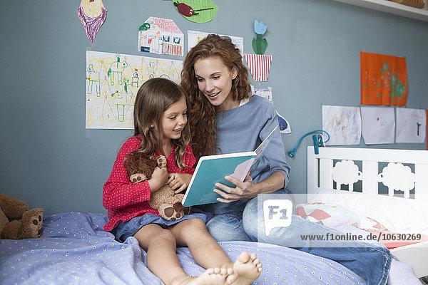 Mutter und kleine Tochter sitzen zusammen auf dem Bett im Kinderzimmer und lesen ein Buch.