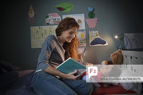 Mutter liest eine Gutenachtgeschichte für ihre kleine Tochter.