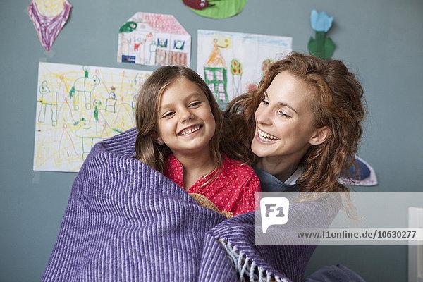 Porträt der glücklichen Mutter und der kleinen Tochter im Kinderzimmer