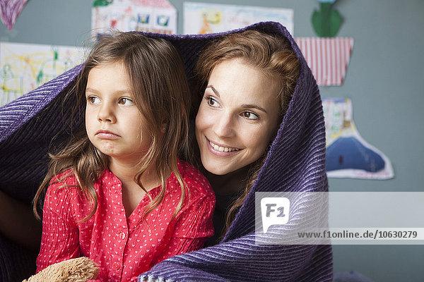 Porträt der lächelnden Mutter und ihrer unglücklichen kleinen Tochter im Kinderzimmer
