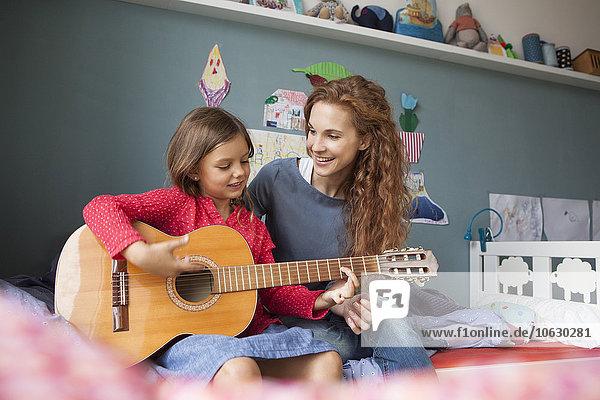 Kleines Mädchen spielt Gitarre  während ihre Mutter zuhört.