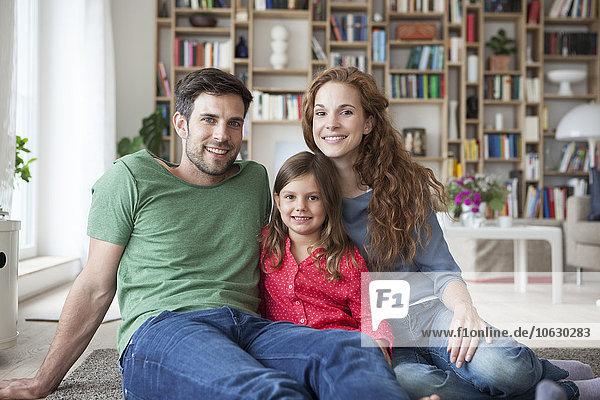 Porträt eines kleinen Mädchens und ihrer Eltern  die zusammen auf dem Boden im Wohnzimmer sitzen.
