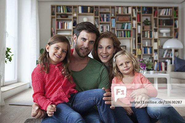 Familienporträt eines Paares mit zwei kleinen Mädchen auf dem Boden des Wohnzimmers