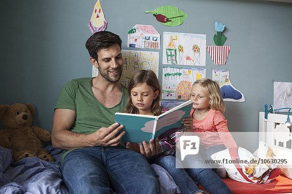 Vater und seine kleinen Töchter sitzen zusammen auf dem Bett im Kinderzimmer und lesen ein Buch.