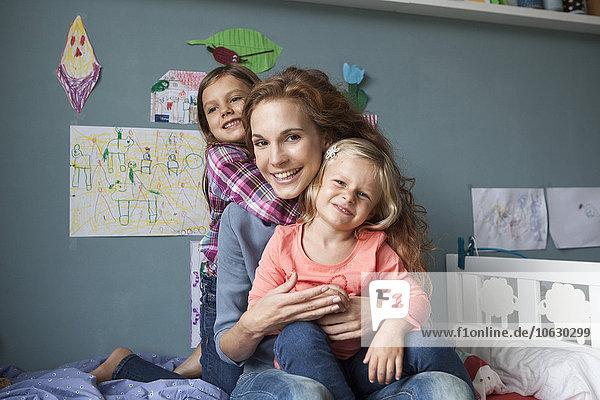 Porträt einer Frau mit ihren kleinen Töchtern im Kinderzimmer