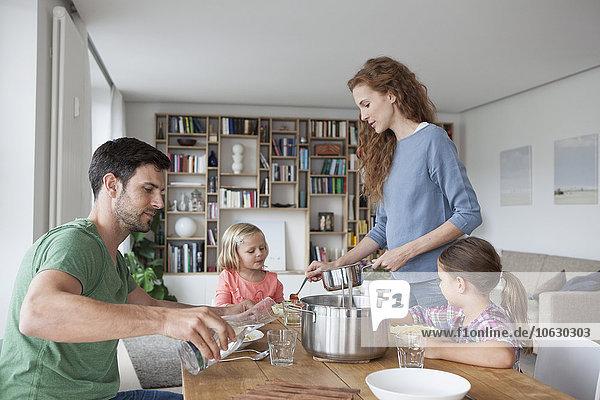 Paar mit zwei Kindern  die zusammen zu Hause zu Mittag essen gehen.