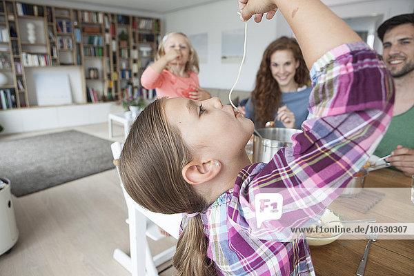 Ein kleines Mädchen isst Spaghetti  während ihre Eltern und ihre Schwester sie beobachten.