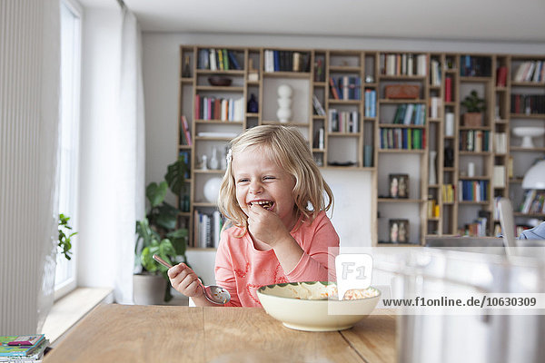 Portrait of laughing little girl eating spaghetti