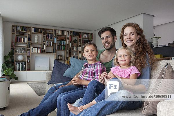 Familienporträt eines Paares mit zwei kleinen Mädchen auf der Couch im Wohnzimmer