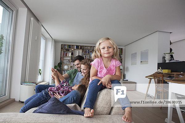 Porträt eines kleinen Mädchens  das auf der Rückenlehne der Couch sitzt  mit seiner Familie im Hintergrund.