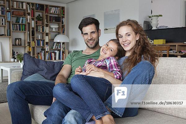 Portrait des glücklichen Paares und der kleinen Tochter auf der Couch zu Hause