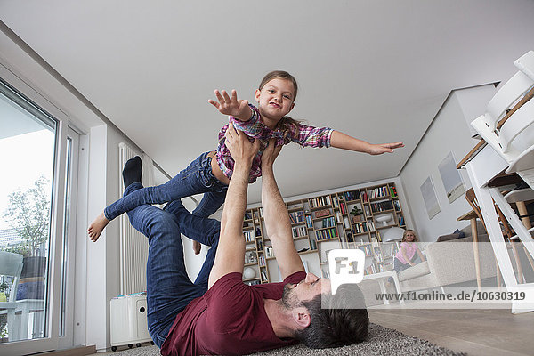 Mann liegt auf dem Boden und spielt mit seiner kleinen Tochter.