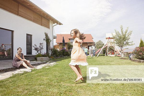 Verspieltes Mädchen mit Familie im Garten