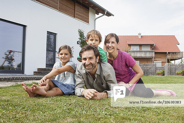 Portrait of smiling family of four in garden