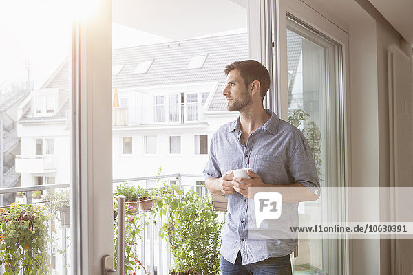 Ernsthafter Mann  der aus dem Fenster schaut.