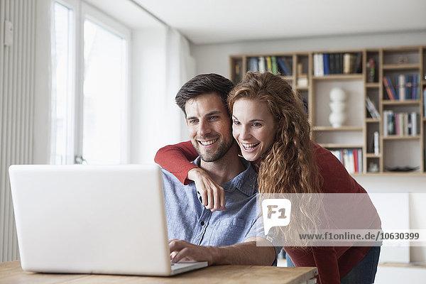 Glückliches Paar zu Hause mit Blick auf den Laptop
