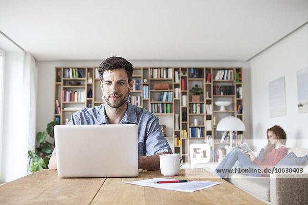 Mann zu Hause mit Laptop und Frau im Hintergrund