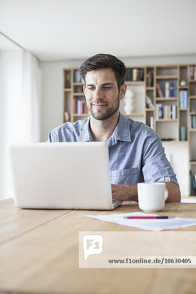 Lächelnder Mann zu Hause mit Laptop