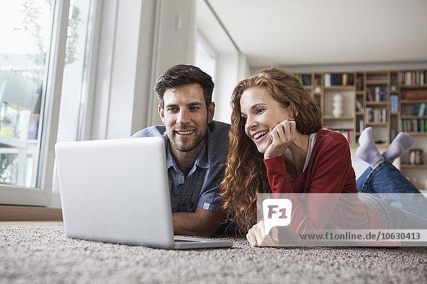 Glückliches Paar auf dem Boden liegend mit Laptop