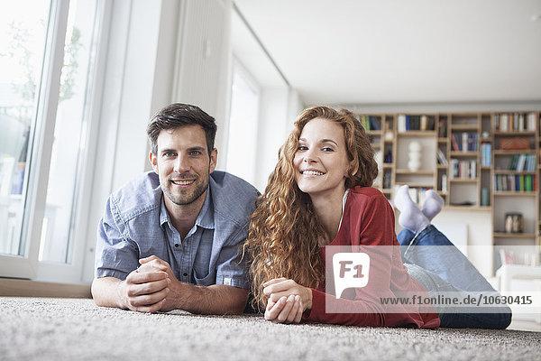 Glückliches Paar auf dem Boden liegend