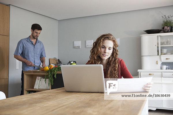 Frau zu Hause mit Laptop und Mann im Hintergrund schneiden Gemüse