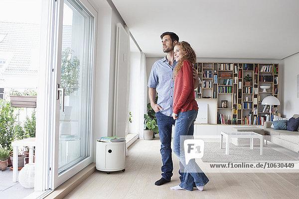 Paar im Wohnzimmer mit Blick aus dem Fenster