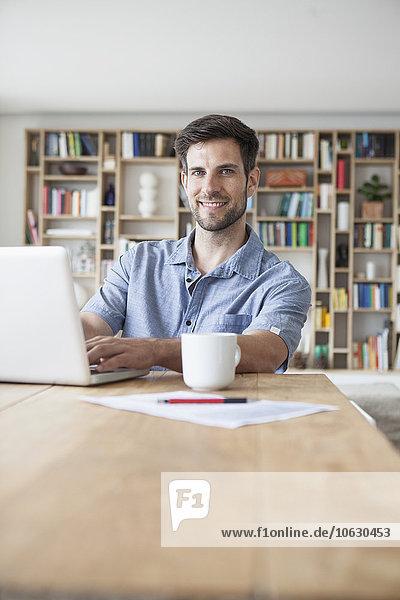 Porträt eines lächelnden Mannes zu Hause mit Laptop