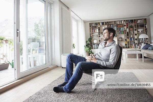 Mann zu Hause im Sessel sitzend aus dem Fenster schauend
