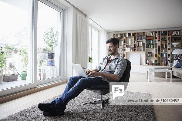 Mann zu Hause sitzend im Sessel mit Laptop