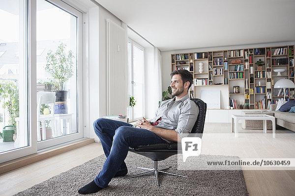 Lächelnder Mann zu Hause im Sessel sitzend aus dem Fenster schauend