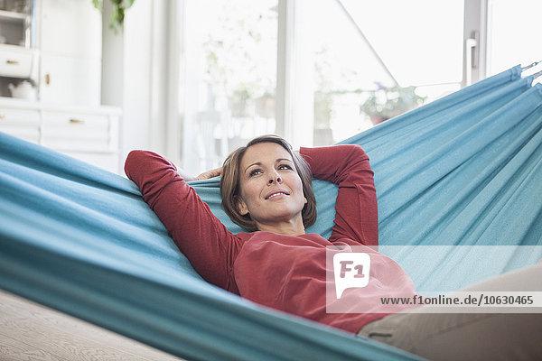 Lächelnde Frau zu Hause in der Hängematte liegend