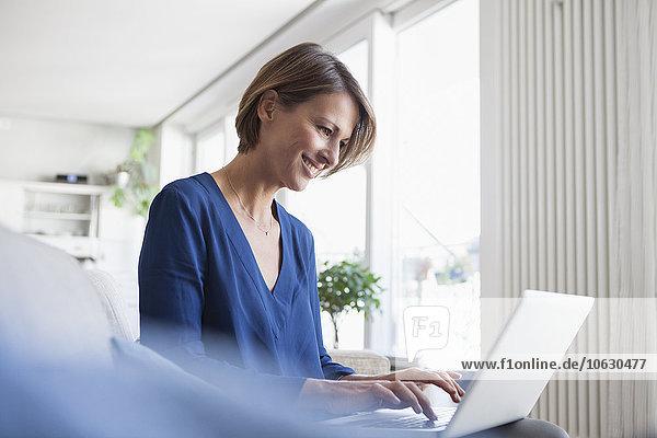 Lächelnde Frau zu Hause sitzend auf der Couch mit Laptop