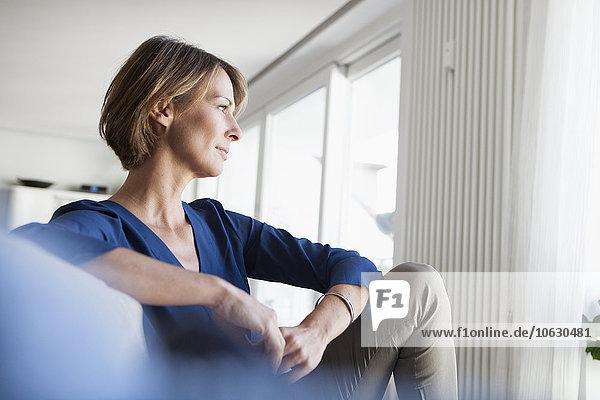 Frau zu Hause auf der Couch sitzend  nachdenkend