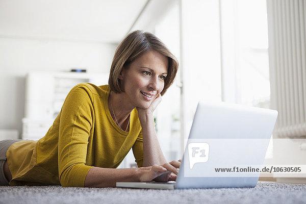 Entspannte Frau zu Hause auf dem Boden liegend mit Laptop