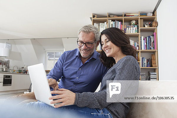 Smiling couple at home on couch using laptop