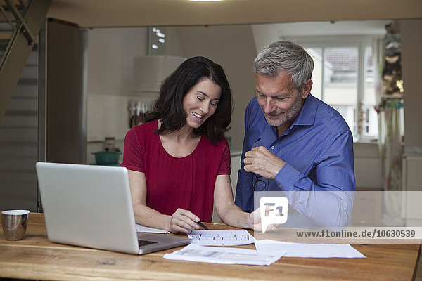 Smiling couple at home with laptop and papers at table
