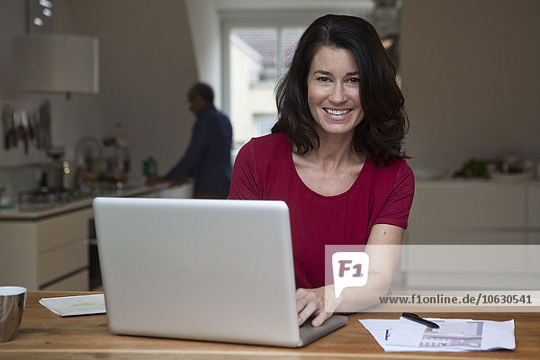 Smiling woman at home using laptop with man in background