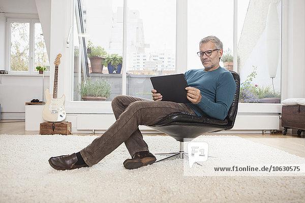 Erwachsener Mann zu Hause im Sessel sitzend mit digitalem Tablett