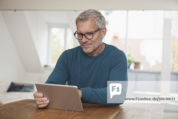 Reifer Mann zu Hause mit digitalem Tablett