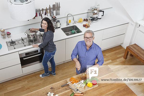 Reife Paare bereiten Gemüse in der Küche zu.