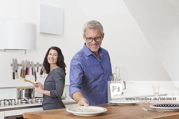 Ein reifes Paar kocht in der Küche mit Frau und Mann  der den Tisch deckt.