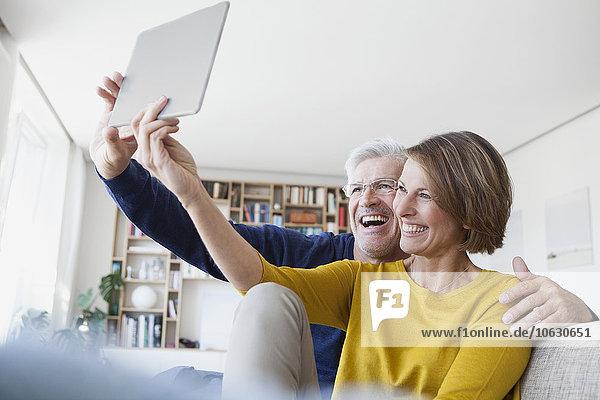 Glückliches Paar  das zu Hause auf der Couch sitzt und einen Selfie mit digitalem Tablett nimmt.