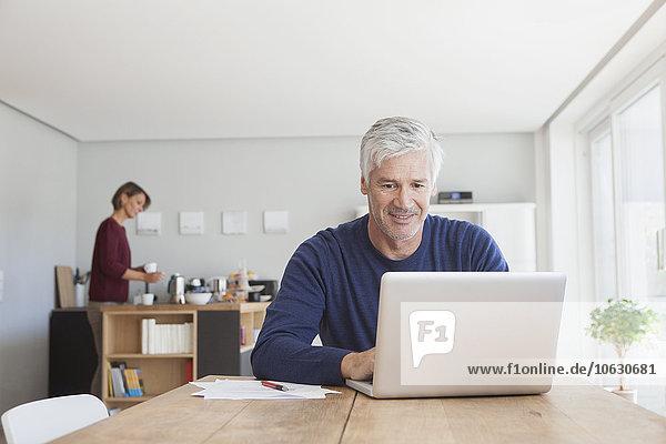 Erwachsener Mann mit Laptop zu Hause
